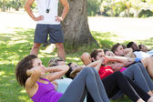Fitness group doing sit ups in park with coach — Stock Photo