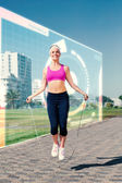 Fit blonde skipping rope on the pier — Stock Photo