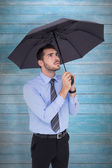 Anxious businessman sheltering with umbrella — Stock Photo