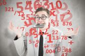 Geeky shrugging businessman biting calculator — Stock Photo
