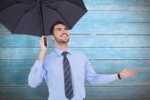 Businessman sheltering with a black umbrella — Stock Photo