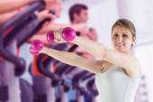 Fit young woman holding weights — Stok fotoğraf