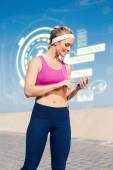 Blonde standing on the promenade against fitness interface — Stock Photo
