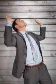 Businessman standing with arms pressing up — Stock Photo