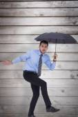 Anxious businessman under umbrella balancing — Stock Photo