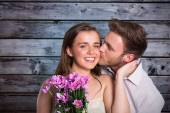 Man kissing woman as she holds flowers — Foto de Stock