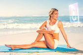 Fit blonde in seated yoga pose on beach — Stock Photo