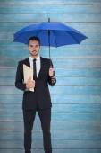 Businessman holding file under umbrella — Stock Photo