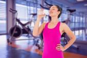 Woman taking a drink against spin bikes — Stock Photo