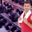 Fit man against collection of barbells — Stock Photo #69031841