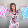 Woman in floral dress holding up shopping bags — Stock Photo #69031883