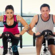 Young man and woman working out at spinning — Stok fotoğraf #69032951