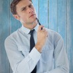 Thinking businessman holding pen — Stock Photo #69036823