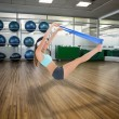 Woman exercising with a blue yoga belt — Stock Photo #69036855