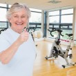 Woman showing thumbs up against exercise bikes — Stock Photo #69039771