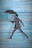 Businessman walking and holding umbrella — Stock Photo