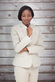 Thinking businesswoman against wooden planks — Stock Photo