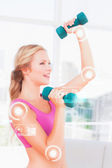 Toned blonde lifting dumbbells and smiling — Stock Photo
