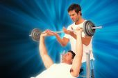 Trainer helping man to lift barbell bench — Stock Photo