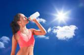 Healthy woman drinking water against sky — Stock Photo