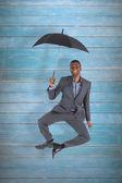 Businessman smiling and holding umbrella — Stock Photo
