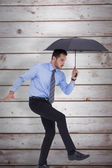 Businessman holding umbrella and balancing — Stock Photo