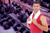 Fit man against collection of barbells — Stock Photo