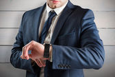 Businessman checking the time on watch — Stock Photo
