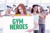 Redhead showing a poster against gym heroes — Stock Photo