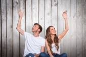 Young couple with hands raised — Stock Photo