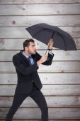 Businessman holding umbrella to protect himself — Stock Photo
