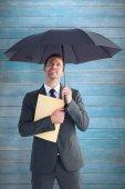 Businessman sheltering under umbrella — Stock Photo