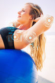 Fit blonde doing sit ups on exercise ball — Stock Photo