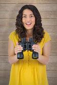Smiling casual woman holding binoculars — Stock Photo