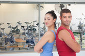 Fit man and woman against empty spin studio — Stock Photo