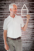 Happy man holding house outline — Stock Photo