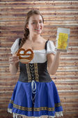 Oktoberfest girl holding beer and pretzel — Stock Photo
