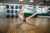 Woman exercising with a blue yoga belt — Stock Photo