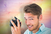 Young man holding digital camera — Stock Photo