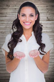 Pretty brunette holding out hands — Stockfoto