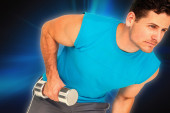 Fit young man exercising with dumbbell — Stock Photo