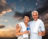 Feliz pareja ajuste contra el cielo azul y naranja — Foto de Stock