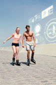 Fit couple rollerblading on the promenade — Stock Photo