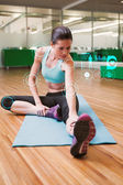 Fit brunette warming up in fitness studio — Stock Photo
