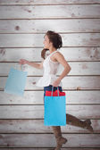 Brunette leaping with shopping bags — Stock Photo