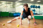 Smiling man warming up in fitness studio — Stock Photo