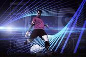 Composite image of goalkeeper kicking ball — Stock Photo