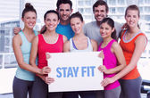 Stay fit against fit smiling people holding blank board — Stock Photo