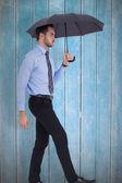 Focused businessman under umbrella stepping — Stock Photo