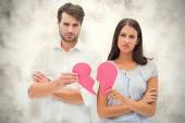 Composite image of upset couple holding two halves of broken hea — Stock Photo